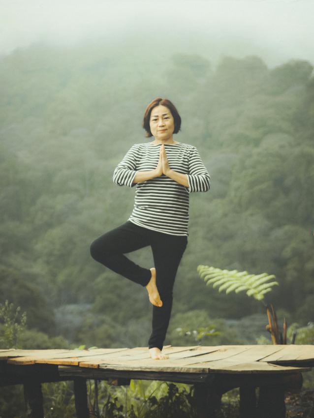 Asiatische Frau in der Baum-Pose des Yoga auf einer Holzbrücke mit Urwald im Hintergrund.